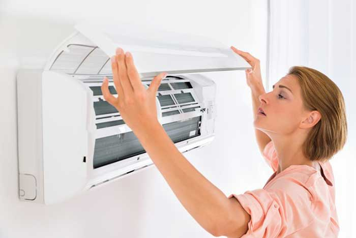 Young Beautiful Woman Opening Air Conditioner At Home
