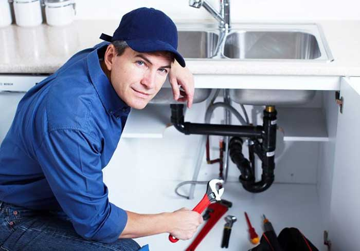 plumber in blue shirt repairing washbasin